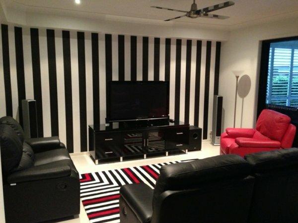 Вертикальная полоса зрительно делает потолки выше и идеально выделяет видеозону комнаты
