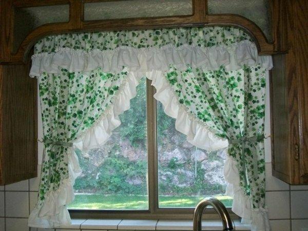 Короткие шторы с мелким природным рисунком, подвязанные в разные стороны, создают домашнюю уютную атмосферу