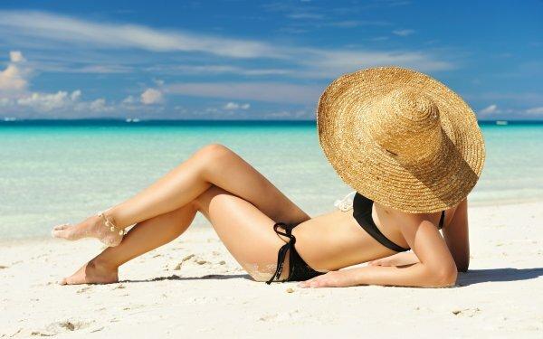 Загадочная девушка в шляпе и купальнике на берегу лазурного океана