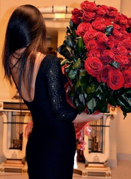 Жгучая брюнетка в красивом черном платье явно заслуживает столь же шикарного букета роз
