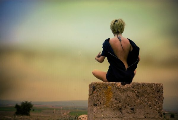 Фото девушки, сидящей на камне, выглядит так же загадочно, как и ее тату в египетском стиле