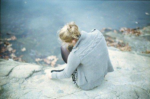 Задумчивая девушка осенью на берегу реки
