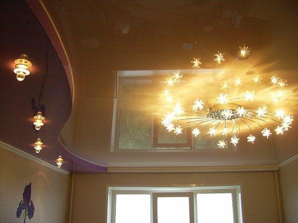Светлый глянцевый потолок, у которого есть центральное освещение, придаст гостиной аккуратный вид