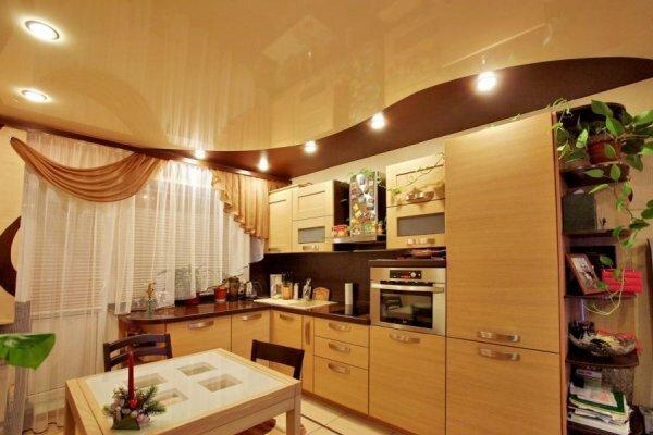 Для удобства хозяйки точечное освещение натяжного потолка направлено на рабочую зону