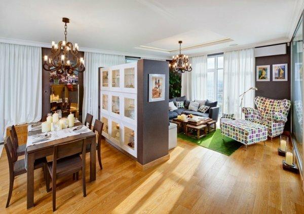 Оригинальный двухсторонний шкаф разделяет комнату на зону отдыха и столовую