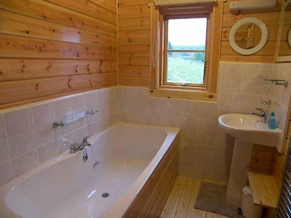 Сочетание деревянных стен дома с наполовину уложенной плиткой