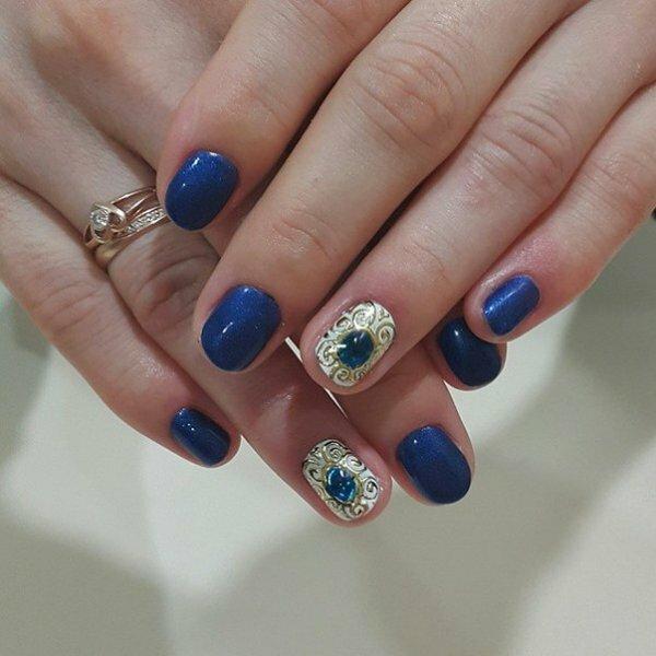 Яркий переливающийся синий гель-лак в сочетании с жидкими камнями и золотой росписью смотрится выигрышно