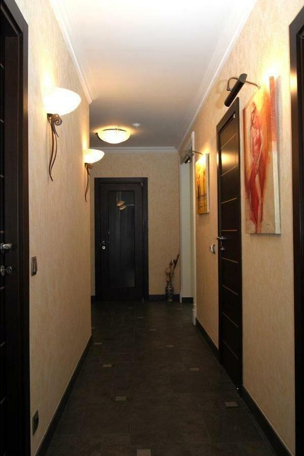 Длинный коридор смотрелся бы скучно, если бы не декоративные светильники и картины