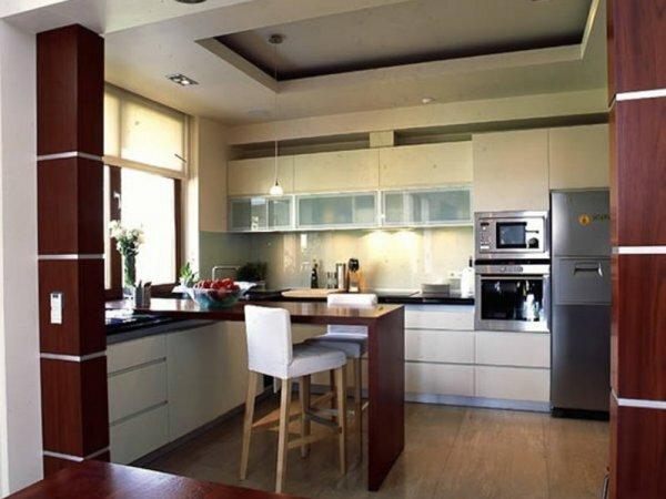 Навесной потолок отделяет кухонную зону от столовой в кухне-студии